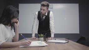De werkgever trok een grafiek op een flipboard en geeft instructies aan zijn ondergeschikte zitting bij de lijst en het neerschri stock video