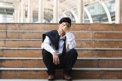 De werklozen beklemtoonden de jonge Aziatische bedrijfsmens die aan strenge depressie lijden Mislukking en ontslagconcept stock fotografie