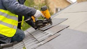 De werkman die pneumatisch spijkerkanon gebruiken installeert tegel in aanbouw op dak van nieuw huis royalty-vrije stock afbeeldingen