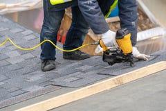 De werkman die pneumatisch spijkerkanon gebruiken installeert tegel in aanbouw op dak van nieuw huis royalty-vrije stock fotografie