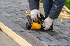 De werkman die pneumatisch spijkerkanon gebruiken installeert tegel in aanbouw op dak van nieuw huis royalty-vrije stock afbeelding
