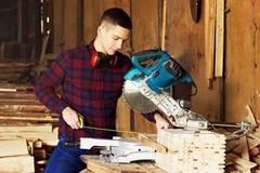 De werkman kleedde zich in het geruite overhemd die met meetlint dichtbij cirkelzaag werken Hout op achtergrond stock fotografie