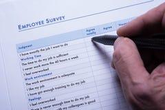 De werknemer beantwoordt de vragen van het werknemersonderzoek op papier Stock Afbeeldingen