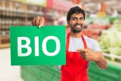 De werknemer die van de kruidenierswinkelopslag bioproducten adverteren royalty-vrije stock foto's