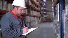 De werknemer herschrijft de goederen in het logistiekpakhuis 4K langzame mo stock videobeelden