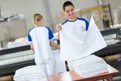 De werknemer keurt het strijken textiel goed stock afbeelding