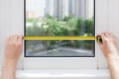 De werknemer maakt een meting van het glas in een plastic venster gebruikend een meetlint stock foto's