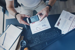 De werknemer neemt schot van grafieken gebruikend smartphone stock foto