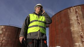 De werknemer spreekt dichtbij telefonisch aan de tanks stock video