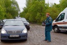 De werknemer van het Ministerie van Noodsituatiesituaties van Rusland regelt de beweging van auto's op de weg dichtbij Moskou Stock Afbeelding