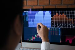 De werknemers analyseren de grafiek van de effectenbeurs gebruikend een pen richtend aan het computerscherm stock afbeelding