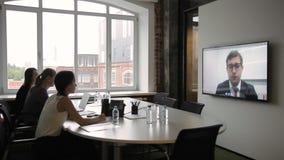 De werknemers houden vergadering door videoconfereren op plasma stock videobeelden