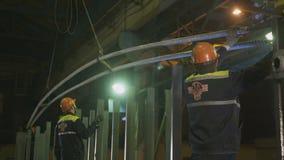 De werknemers installeren kabels in karkas en werkende lasser stock footage