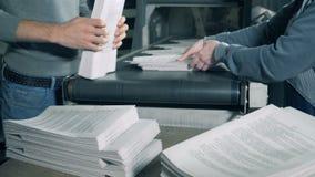 De werknemers stapelen opgevouwen gedrukt document op stock videobeelden
