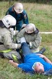 De werknemers van het Ministerie van Noodsituatiesituaties verstrekken eerste hulp aan het slachtoffer royalty-vrije stock foto
