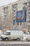 De werknemers van het reclamebureau kleven banner op een straataanplakbord Stock Fotografie