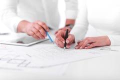 De werknemers werken aan blauwdrukken of techniekplannen in het bureau techniek stock fotografie