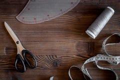 De werkplaats van de kledingsontwerper Het meten van band, draad en sciccors op donkere houten lijst hoogste mening als achtergro Royalty-vrije Stock Afbeelding
