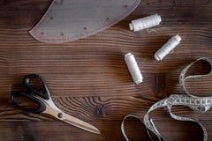 De werkplaats van de kledingsontwerper Het meten van band, draad en sciccors op donkere houten lijst hoogste mening als achtergro Stock Foto