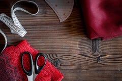 De werkplaats van de kledingsontwerper Stof, die band en sciccors op donkere houten lijst hoogste mening meten als achtergrond Royalty-vrije Stock Fotografie