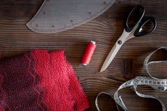 De werkplaats van de kledingsontwerper Stof het meten van band, draad en sciccors op donkere houten lijst hoogste mening als acht Stock Afbeelding