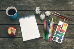 De werkplaats van de kunstenaar Never geeft op Kop van hete koffie, blocnote met leeg blad van document, kleurpotloden, verf, bor Stock Afbeeldingen