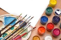 De werkplaatsschilder, borstelt ter beschikking, kruiken met gouache, canvas voor het schilderen, palet, het achtergrondart. Stock Foto