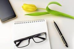 De werkruimte op lijst is tulp, notitieboekje, glazen, smartphone en pen Stock Afbeelding