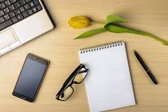 De werkruimte op de lijst is tulp, notitieboekje, laptop, glazen, smartphone en pen Royalty-vrije Stock Afbeeldingen