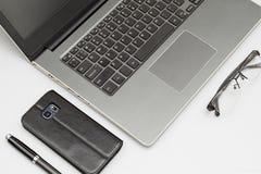 De werkruimtesamenstelling van laptop computer, de smartphonepen, en de gevouwen glazen op bureau dienen achtergrond in Gestapeld stock afbeeldingen