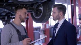 De werktuigkundige adviseert klant en maakt nota's in klembord status onder auto opgeheven op lift in de autodienst stock video