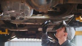 De werktuigkundige controleert de bodem van auto in garage de automobiele dienst, omhoog sluit Stock Afbeeldingen