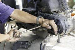 De werktuigkundige controleert de katrol en de riem van motorfiets stock foto's