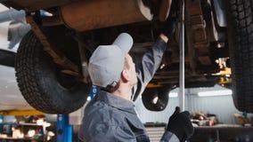 De werktuigkundige controleert de opschorting in de garage automobiele dienst stock foto