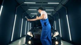 De werktuigkundige danst met hulpmiddelen in zijn handen dichtbij een auto stock videobeelden