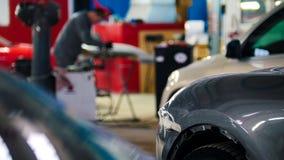 De werktuigkundige in de autodienst die en detail van auto bevestigen herstellen, defocused achtergrond Royalty-vrije Stock Foto's