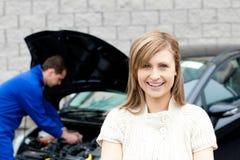 De werktuigkundige die van de garage een auto herstelt Stock Foto's