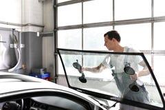 De werktuigkundige in een garage vervangt gebrekkig windscherm van een auto royalty-vrije stock fotografie