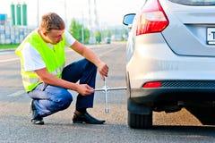 De werktuigkundige in een vest bindt het wiel aan de auto op de weg Royalty-vrije Stock Foto