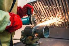 de werktuigkundige maakt een gelaste naad op een sectie van een staal schoon een malende machine in de metaalworkshop stock afbeeldingen