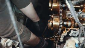 De werktuigkundige maakt en veegt de motor van een autodelen schoon af stock afbeelding