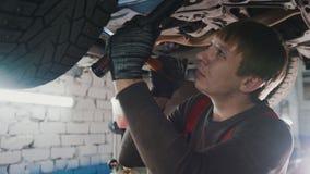 De werktuigkundige met de lamp controleert de bodem van auto in garage de automobiele dienst, omhoog sluit Stock Foto's