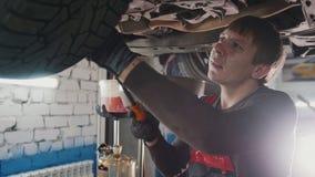 De werktuigkundige met de lamp controleert de bodem van auto in garage de automobiele dienst, omhoog sluit Stock Fotografie