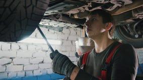De werktuigkundige met de lamp controleert de bodem van auto in garage de automobiele dienst, omhoog sluit Royalty-vrije Stock Afbeeldingen