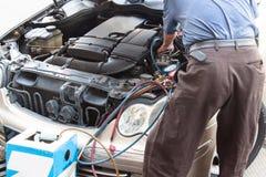 De werktuigkundige met manometer het vullen gas in autovoertuig lucht-condit-lucht stock fotografie