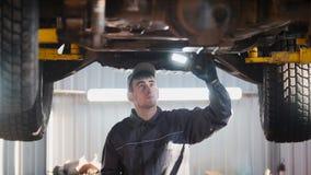 De werktuigkundige met thr lamp controleert de bodem van auto in de garage automobiele dienst, brede hoek Royalty-vrije Stock Fotografie