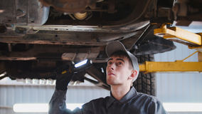 De werktuigkundige met thr lamp controleert de bodem van auto in garage de automobiele dienst, omhoog sluit Stock Foto