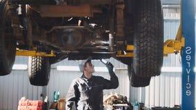 De werktuigkundige met thr lamp controleert de bodem van SUV-auto in de garage automobiele dienst, brede hoek Stock Afbeelding