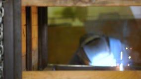 De werktuigkundige stijgt het lassenmasker op en bekijkt het resultaat van zijn werk stock videobeelden