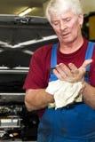 De werktuigkundige van de auto, die zijn handen schoonmaakt Stock Foto